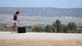 Молодая женщина в белых шортах сидя на чемодане, после этого идет вдоль дороги видеоматериал