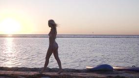 Молодая женщина в бикини идет на пляж и представляет во время захода солнца видеоматериал