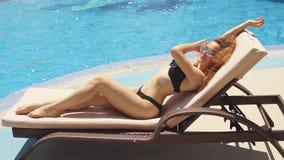 Молодая женщина в бикини лежа на задней части дальше sunbed около волн голубого моря сток-видео