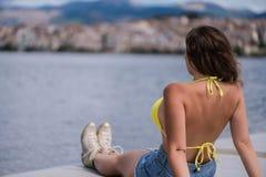 Молодая женщина в бикини на деревянном мосте на городке кастории и предпосылке озера Orestias Греция Стоковые Фотографии RF