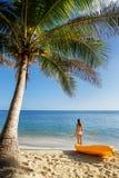 Молодая женщина в бикини стоя на песчаном пляже с каяком и затвором моря стоковая фотография rf