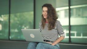Молодая женщина в видео джинсов вызывая к ее другу сидя снаружи сток-видео
