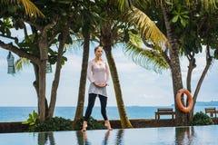 Молодая женщина в гетры и тунике делает практику йоги, раздумье, стоя представление на бассейне в курорте с ландшафтом океана стоковые фотографии rf