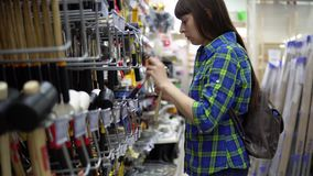 Молодая женщина в голубой checkered рубашке выбирает резиновый мушкел в супермаркете