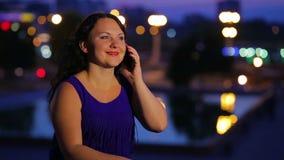 Молодая женщина в голубом платье говорит на smartphone против предпосылки уличных светов запачканных в стороне видеоматериал