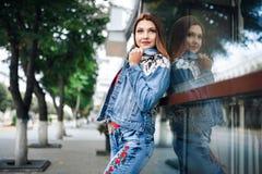 Молодая женщина в голубых джинсах и красной рубашке стоя перед отраженными окнами напольно Стоковое Фото