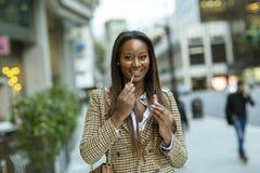 Молодая женщина в городе кладя на lipsgloss стоковые изображения rf
