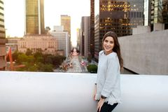 Молодая женщина в городском пейзаже на заходе солнца стоковые фотографии rf