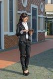 Молодая женщина в деловом костюме с таблеткой стоит на улице стоковое фото rf