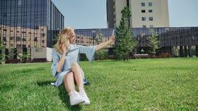 Молодая женщина в джинсах одевает со смартфоном фотографирует акции видеоматериалы