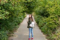Молодая женщина в зеленой куртке и зеленый рюкзак в парке полностью вычисляют от задней части Стоковое фото RF