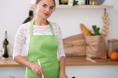 Молодая женщина в зеленой рисберме варит в кухне Фрай домохозяйки мясо в лотке Стоковое Фото