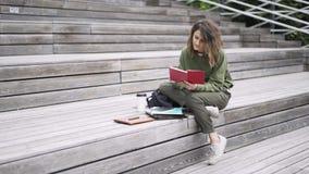 Молодая женщина в зеленом цвете читая книгу на лестницах акции видеоматериалы