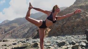 Молодая женщина в йоге bodysuit практикуя на пляже над морем на изумительном восходе солнца Фитнес, спорт, йога и здоровая сток-видео