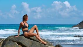 Молодая женщина в йоге bodysuit практикуя на пляже над морем на изумительном восходе солнца Фитнес, спорт, йога и здоровая видеоматериал