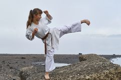 Молодая женщина в карате кимоно практикуя на побережье реки стоковые фото