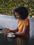 Молодая женщина в кафе занимаясь серфингом сеть на мобильном телефоне стоковая фотография