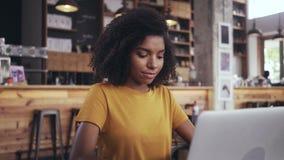 Молодая женщина в кафе используя ноутбук акции видеоматериалы