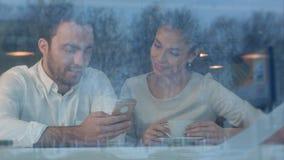 Молодая женщина в кафе печатая ее телефонный номер для красивого человека Стоковое Изображение