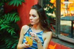 Молодая женщина в кафе улицы со стеклом освежающего напитка стоковое изображение