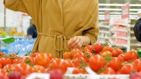 Молодая женщина в коричневой руке пальто принимает красные свежие томаты видеоматериал