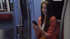 Молодая женщина в костюме отправляя SMS на ее смартфоне пока возвращающ домой поездом сток-видео
