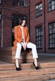 Молодая женщина в красном пальто и белых брюках сидя на деревянной скамье стоковые фотографии rf