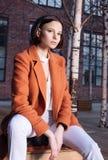 Молодая женщина в красном пальто и белых брюках сидя на деревянной скамье улица стоковые изображения rf