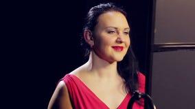 Молодая женщина в красном платье с красной губной помадой усмехается видеоматериал