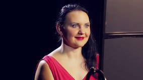 Молодая женщина в красном платье с красной губной помадой усмехается Конец-вверх сток-видео
