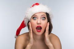 Молодая женщина в красных юбке и шляпе Санта Клауса на светлом backgr Стоковая Фотография RF