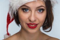 Молодая женщина в красных юбке и шляпе Санта Клауса на светлом backgr Стоковые Фото