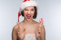 Молодая женщина в красных юбке и шляпе Санта Клауса на светлом backgr Стоковое Изображение