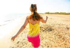 Молодая женщина в красочном платье на пляже в идти вечера Стоковое Изображение