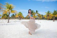 Молодая женщина в купальнике и пропуская юбке, танцуя на карибском пляже стоковая фотография
