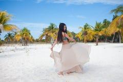 Молодая женщина в купальнике и пропуская юбке, танцуя на карибском пляже стоковое фото