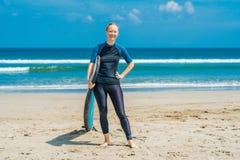 Молодая женщина в купальнике с готовым прибоя для новичков для серфинга взволнованности положительные стоковые фото
