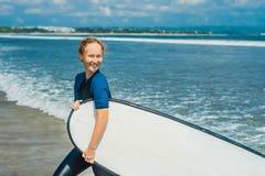 Молодая женщина в купальнике с готовым прибоя для новичков для серфинга взволнованности положительные стоковая фотография rf
