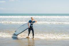 Молодая женщина в купальнике с готовым прибоя для новичков для серфинга взволнованности положительные стоковые изображения