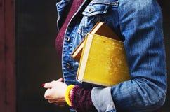 Молодая женщина в куртке джинсов держа кучу книг в ее руке Стоковое Изображение RF