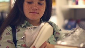 Молодая женщина в магазине выбирает ботинки demi-сезона видеоматериал