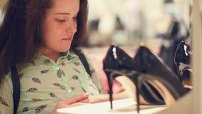 Молодая женщина в магазине выбирает ботинки demi-сезона сток-видео