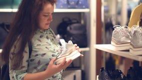 Молодая женщина в магазине выбирает теплые одежды зимы сток-видео
