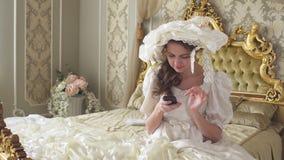 Молодая женщина в мантии шарика сидит на кровати и текстах украшенных золотом на сотовом телефоне Принцесса использует устройство видеоматериал