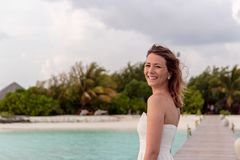 Молодая женщина в медовом месяце ослабляет на пристани смотря заход солнца стоковая фотография rf