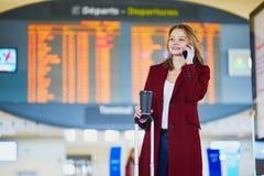 Молодая женщина в международном аэропорте стоковая фотография