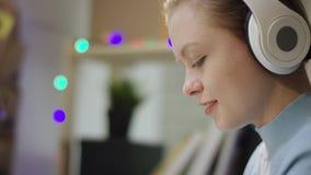 Молодая женщина в наушниках писать домашнюю работу видеоматериал