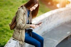 Молодая женщина в обмене текстовыми сообщениями вскользь одежд на таблетке на заходе солнца Стоковое Фото