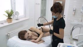 Молодая женщина в офисе cosmetologist делает поднимаясь терапию, замедленное движение сток-видео
