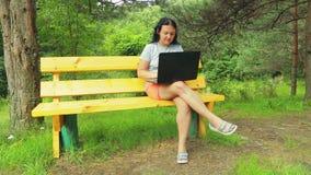 Молодая женщина в парке на стенде работая с компьтер-книжкой Оно управляет прочь насекомыми летания сток-видео